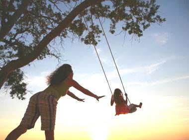 mother pushing daughter on swing