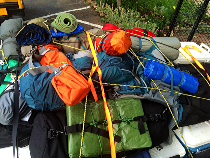 pile of backpacks and tents and gear