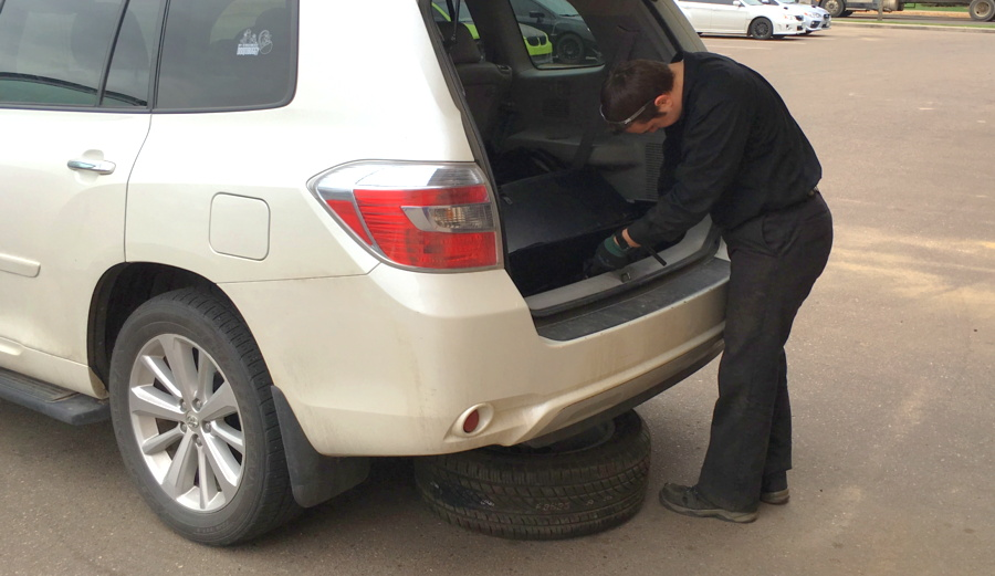 new spare tire being put in position toyota highlander suv