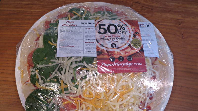 papa murphy's pizza in the plastic wrap, ready to cook