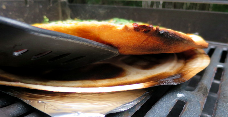 checking bbq grilled pizza with spatula