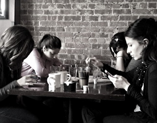 people obsessed with smartphones at dinner table