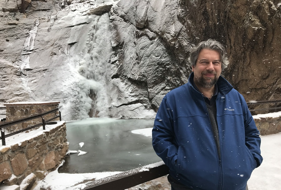 dave taylor standing in front of frozen waterwall, seven falls, broadmoor, colorado springs