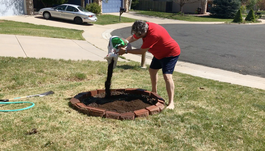 man adding dirt to flower bed