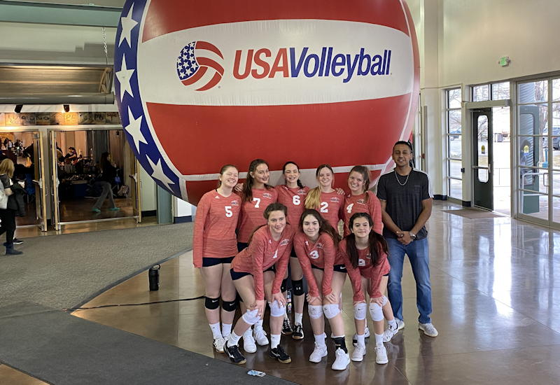 girls club volleyball - team posed in front of usa volleyball ball, greeley co