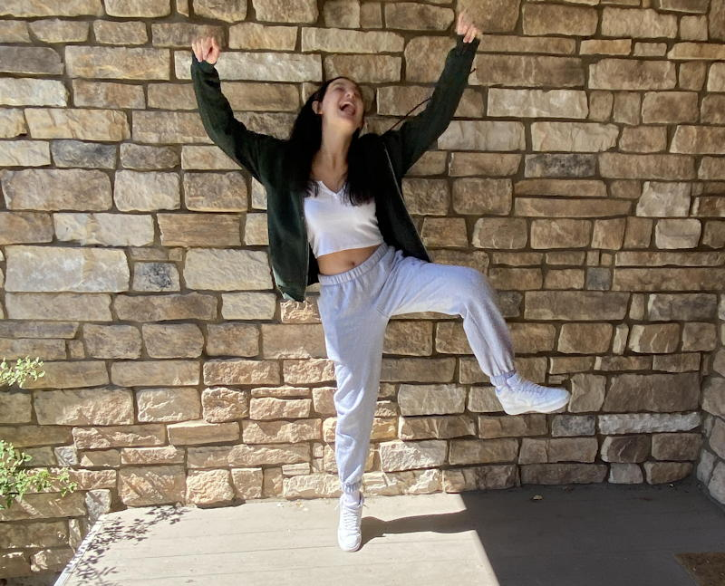 happy girl dancing in front of stone wall