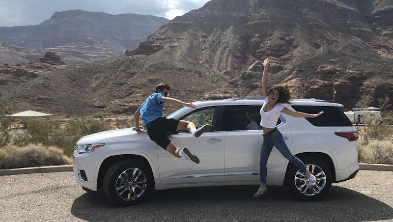 kids jumping in front of white suv, mountains behind